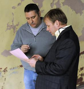 ANDRE TEAGUE/BRISTOL HERALD COURIER — Auctioneer Bart Long, right, goes over the paperwork with Tommy Shrader of Rosedale, VA after Shrader placed the winning bid Saturday morning to purchase the 501 State St. building.