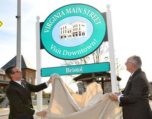 Earl Neikirk/Bristol Herald Courier — Bristol Virginia Mayor Ed Harlow, right, and Jeff Sadler, Virginia Main Street Program Director unveil the new signage during a press conference Friday.